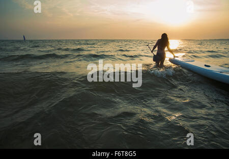 Woman pulling paddleboard in lake - Stock Photo
