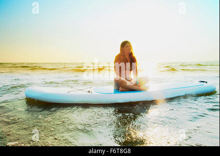 Woman sitting on paddleboard in lake - Stock Photo