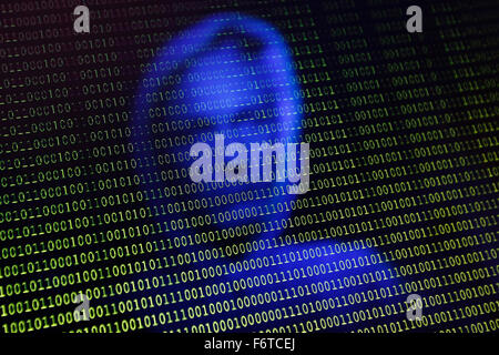 A face is reflected into a computer screen with binary type - Stock Photo