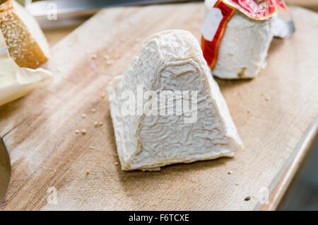 The Wrinkled Rind of a piece of Pouligny St Pierre cheese. A block of cheese on a wooden cutting board. - Stock Photo