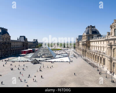 Louvre Pyramid and Paris Beyond. The great glass pyramid in the courtyard of the Louvre Palace with milling tourists - Stock Photo