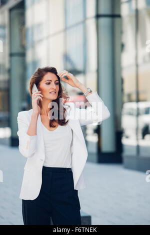 Businesswoman outdoors on cell phone - Stock Photo