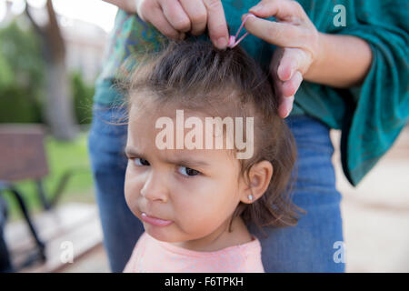 Mother tying up hair of her little daughter, close-up - Stock Photo