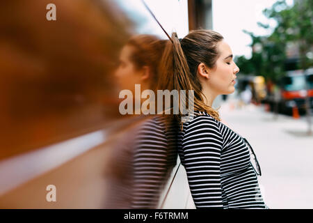 Brunette young woman leaning against wooden wall - Stock Photo