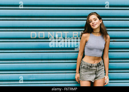 Brunette young woman leaning against shutter - Stock Photo