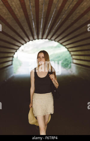 Young woman walking in a tunnel - Stock Photo
