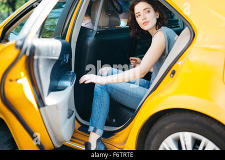 USA, New York City, portrait of  young woman getting on a yellow cab - Stock Photo