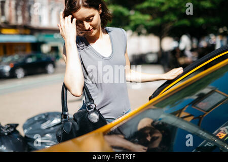 USA, New York City, young woman getting on a yellow cab - Stock Photo