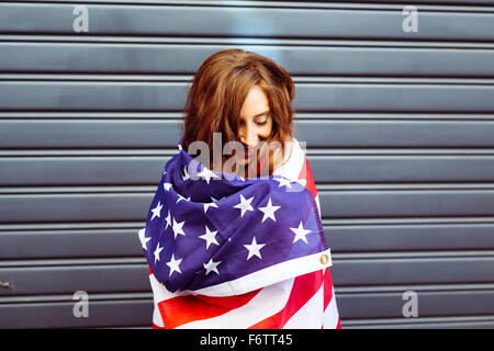 Woman wrapped in an American flag - Stock Photo