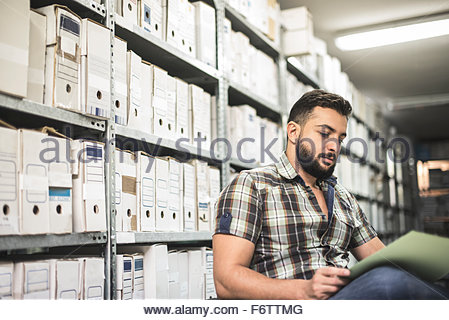 Bearded man working on file in an archive - Stock Photo