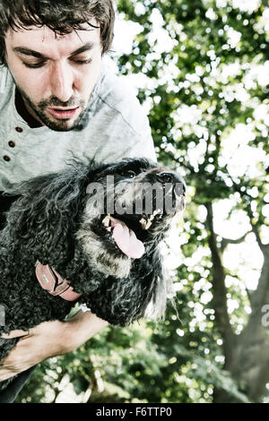 Man playing with his poodle in the garden - Stock Photo
