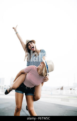 Spain, Barcelona, young woman giving her friend a piggyback ride - Stock Photo