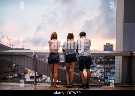 Spain, Barcelona, back view of three friends looking at view from a bridge - Stock Photo