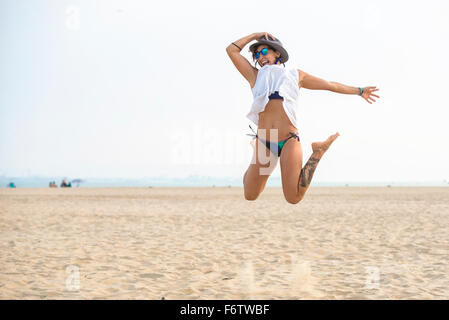 Spain, Cadiz, El Puerto de Santa Maria, Woman jumping on the beach - Stock Photo