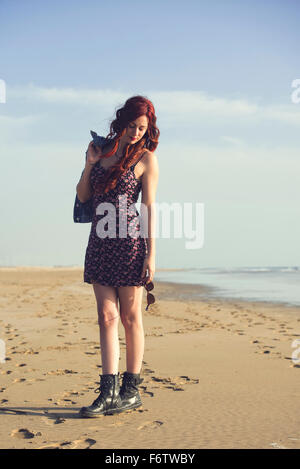 Spain, El Puerto de Santa Maria, portrait of redheaded young woman standing on the beach - Stock Photo