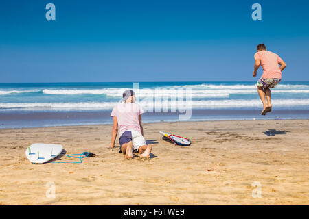 Indonesia, Bali, two surfers doing exercises on the beach - Stock Photo
