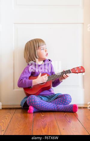 Portrait of little girl sitting on wooden floor playing ukulele - Stock Photo