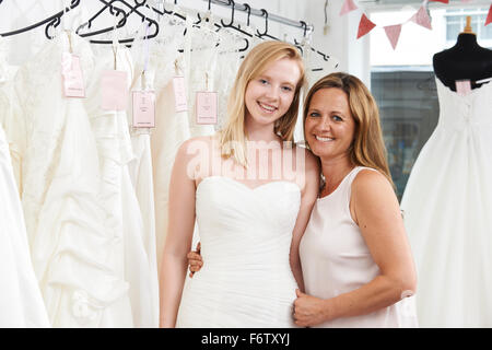 Mother Helping Daughter To Choose Dress In Bridal Store - Stock Photo