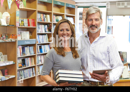 Male And Female Owners Of Bookstore Using Digital Tablet - Stock Photo