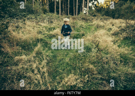 Little boy exploring forest, walking in grass with his stick - Stock Photo
