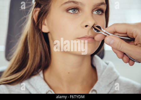 ENT doctor examining teenage girl with nasal speculum - Stock Photo