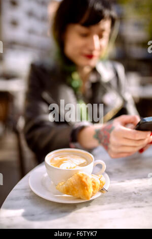 Spain, Gijon, Cup of cappucino, young woman in background using smart phone - Stock Photo