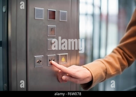 Woman pressing button of a lift - Stock Photo