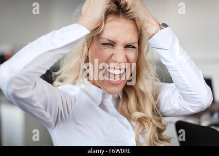 Blond woman in office tearing her hair out - Stock Photo