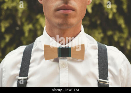 Young man wearing a wooden bow tie, close-up - Stock Photo