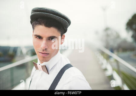 Portrait of young man wearing beret and a wooden bow tie - Stock Photo