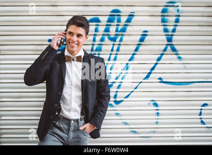 Young man on the phone wearing jacket and a wooden bow tie - Stock Photo