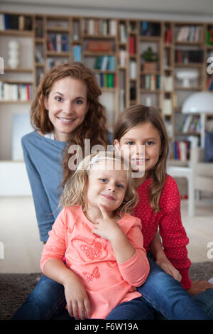 Portrait of two little sisters and her mother in the background sitting on the floor at living room - Stock Photo