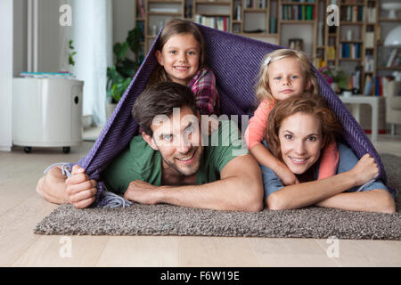Portrait of couple with her little daughters lying together on the floor of the living room covered by a blanket - Stock Photo