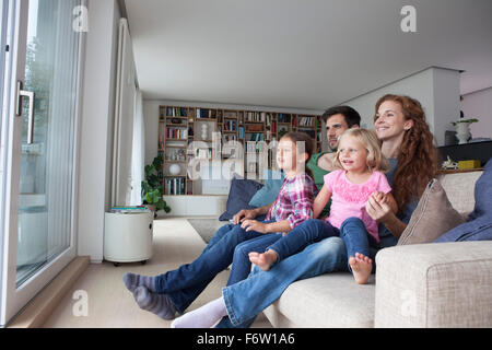 Couple and two little girls sitting on couch in the living room looking through terrace door - Stock Photo