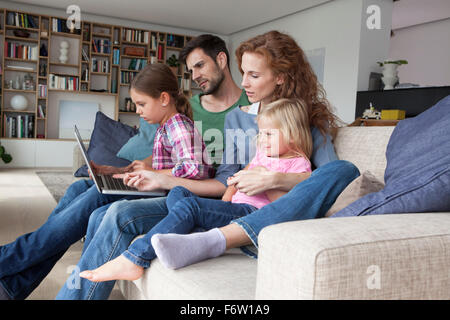 Couple sitting with their with two little daughters on couch in the living room looking at laptop - Stock Photo