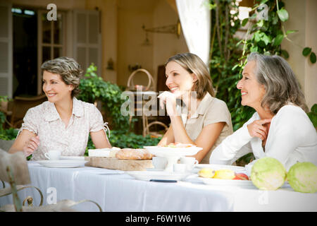 Spain, Mallorca, three female friends sitting at laid table in the garden - Stock Photo