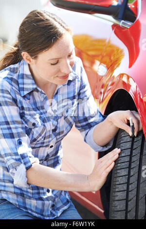 Woman Checking Tread On Car Tyre With Gauge - Stock Photo