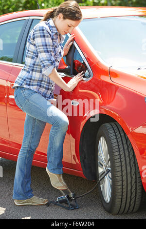 Woman Inflating Car Tyre With Foot Pump Stock Photo