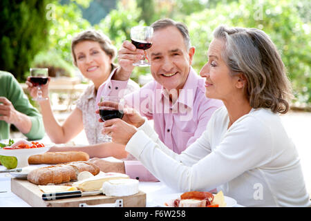 Spain, Mallorca, mature man sitting with friends at laid table in the garden toasting with red wine - Stock Photo