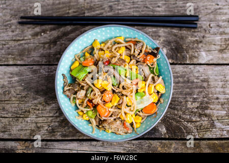 Vegetarian stir-fry with noodles, corn, carrots, mushrooms, sprouts and tofu - Stock Photo