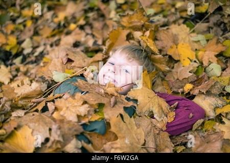 Portrait of smiling boy lying on the ground covered with autumn leaves - Stock Photo