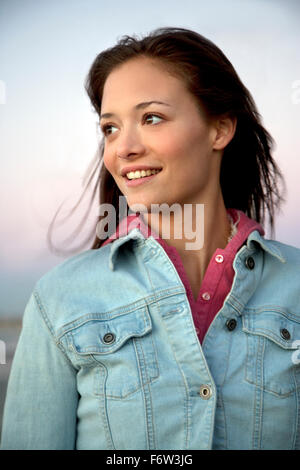Smiling young woman in denim jacket - Stock Photo
