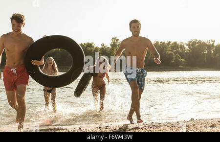 Friends with inner tubes running in river - Stock Photo