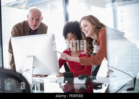 Three colleagues in office looking at computer screen - Stock Photo