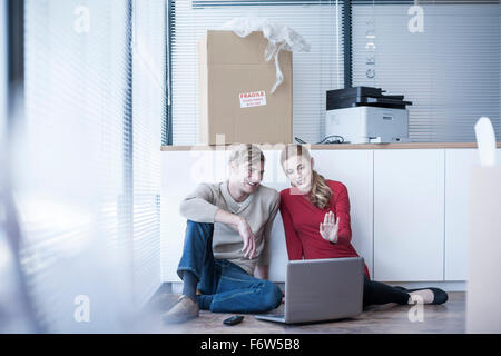 Two colleagues sitting on office floor using laptop - Stock Photo