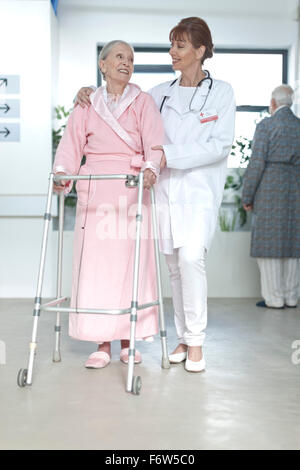 Doctor leading elderly patient with walking frame on hospital floor - Stock Photo
