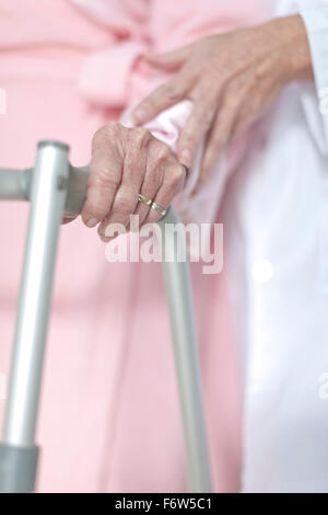 Elderly patient with walking frame being supported - Stock Photo