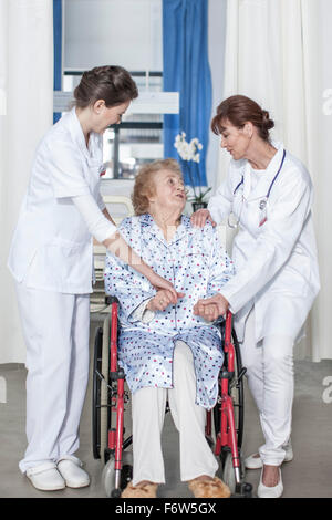 Doctor and nurse caring for elderly patient in wheelchair - Stock Photo