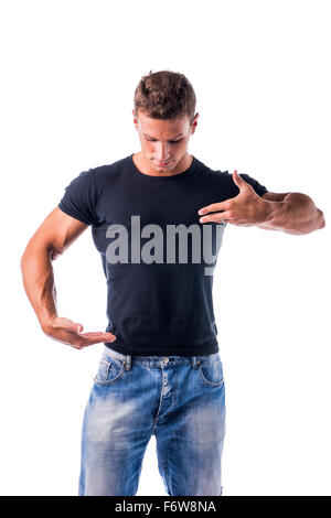 Handsome Muscular Young Man Wearing Casual Black Shirt and Jeans Showing Empty Copy Space on His T-Shirt with Hands - Stock Photo