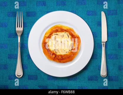 round white plate with pizza, knife and fork on table - Stock Photo